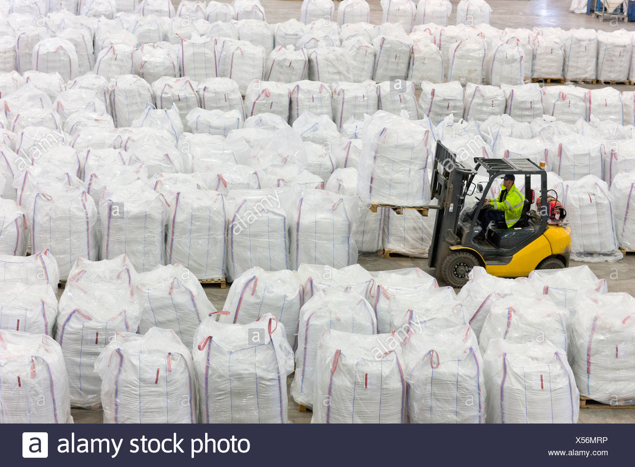 Forklift operator lifting large bag of recycled plastic pellets in warehouse - Stock Image