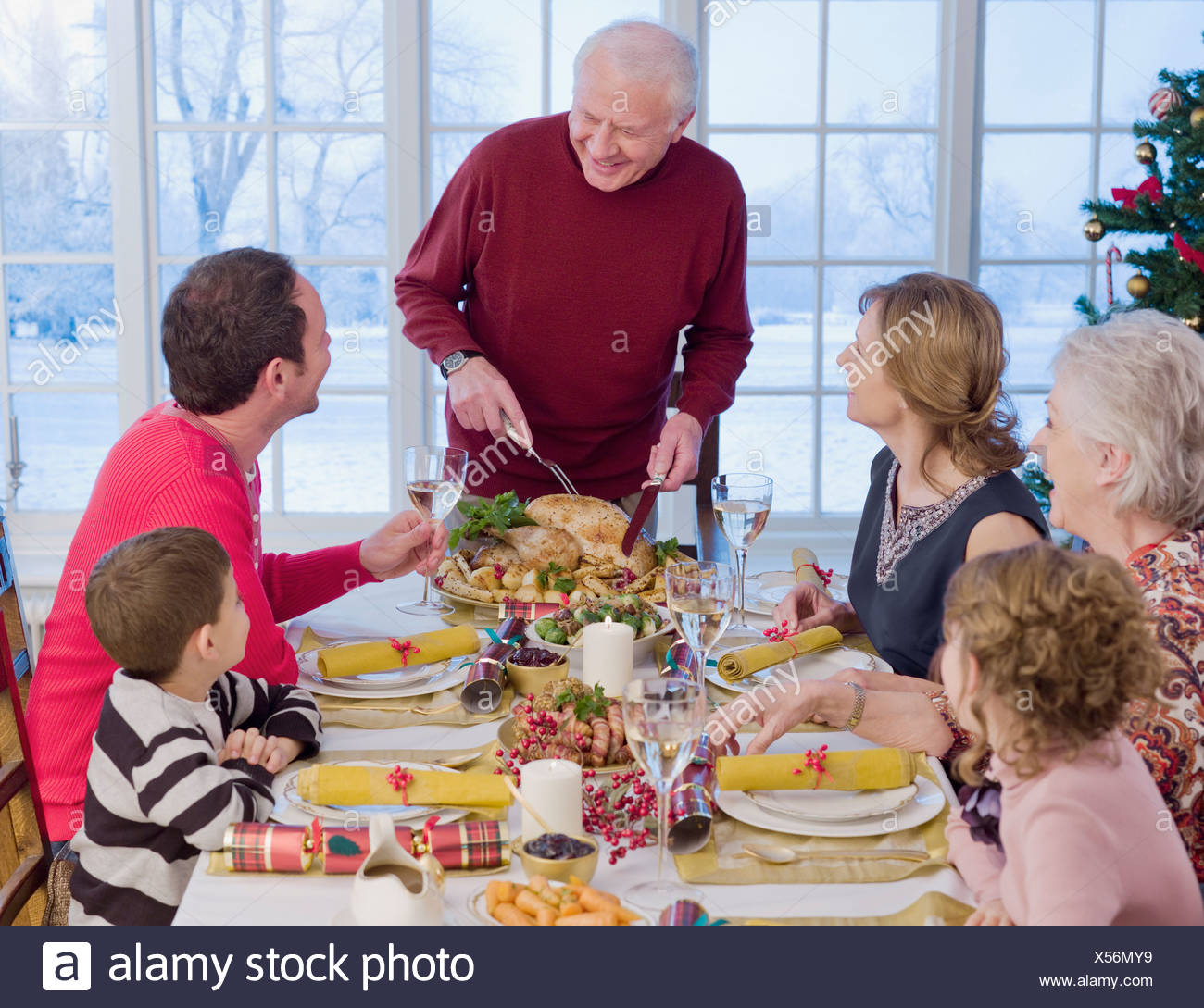 Man carving Christmas turkey at table Stock Photo