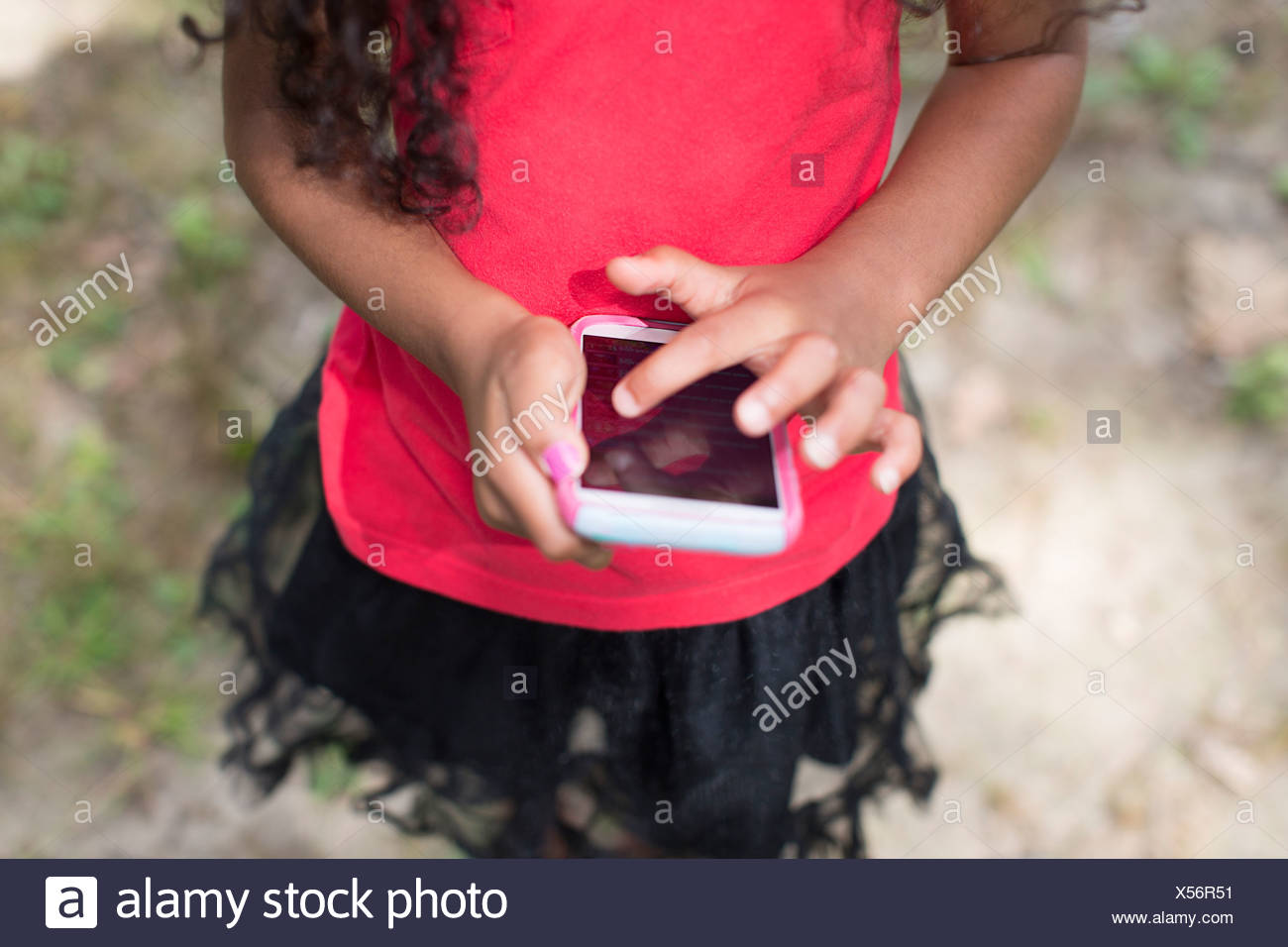 Young girl in park playing hand held video game - Stock Image