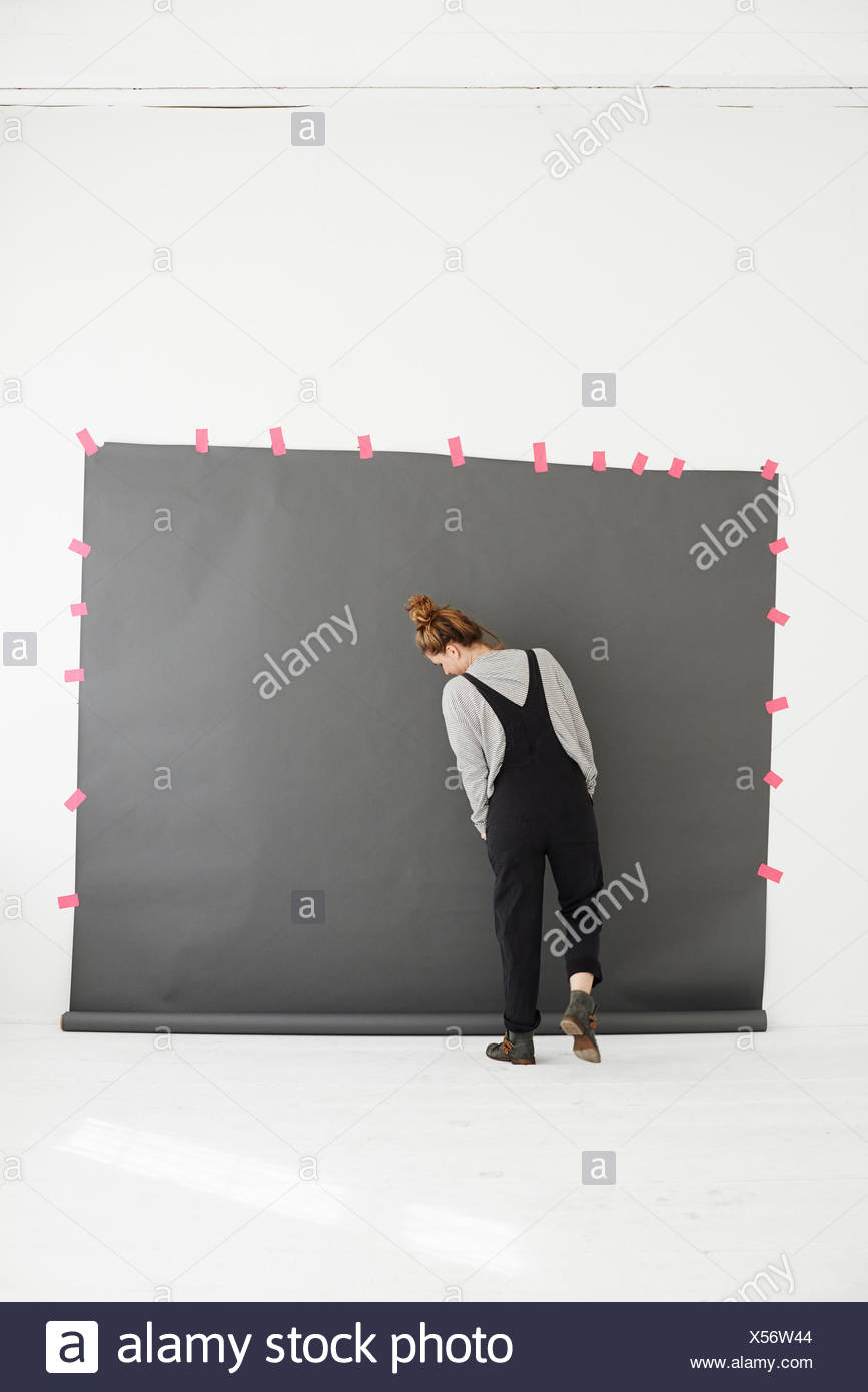Woman in front of photographers backdrop, rear view - Stock Image