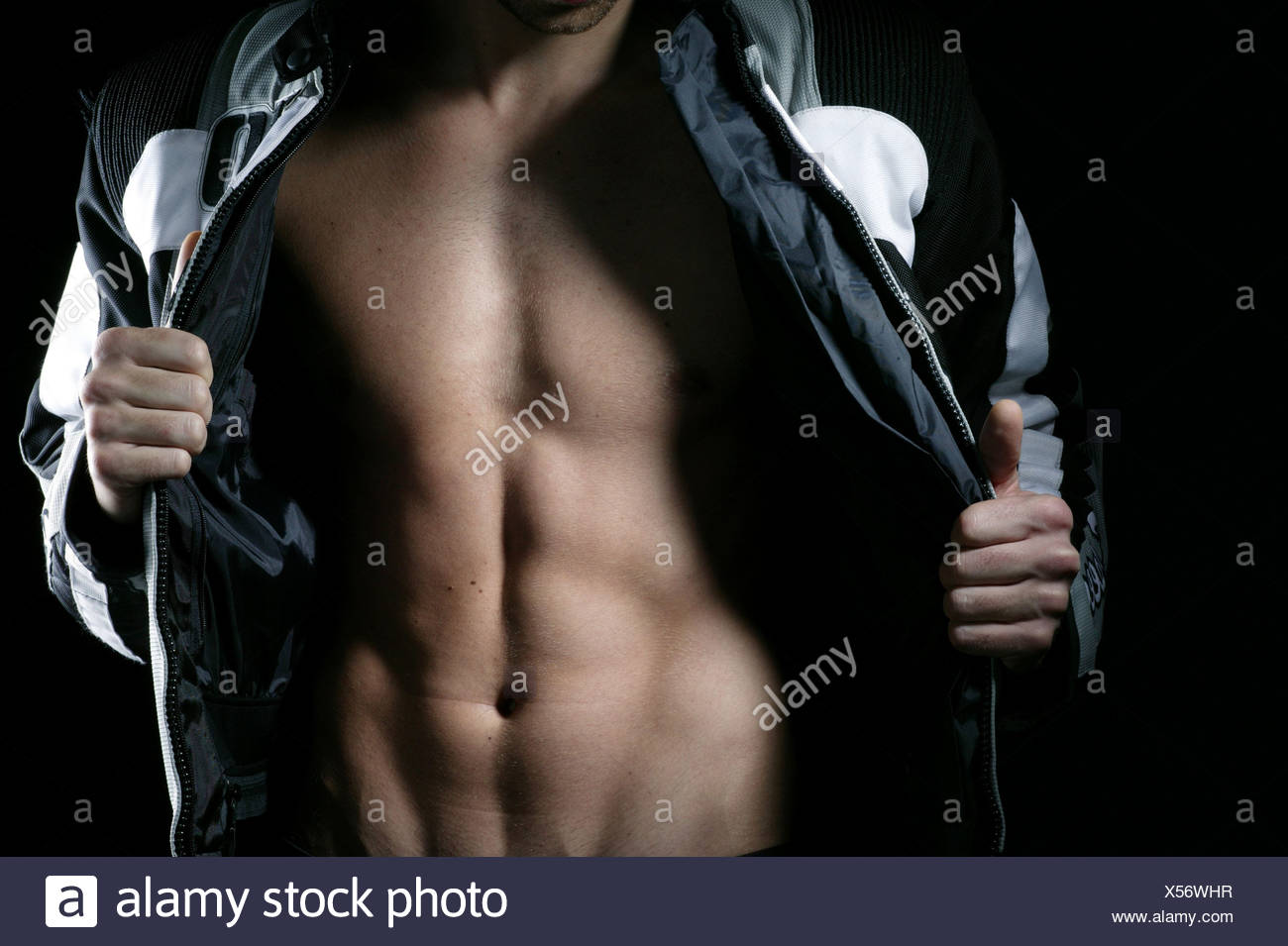 Man jacket openly upper body musculature detail people young stands motorcycle-jacket opened bodies slim muscular - Stock Image