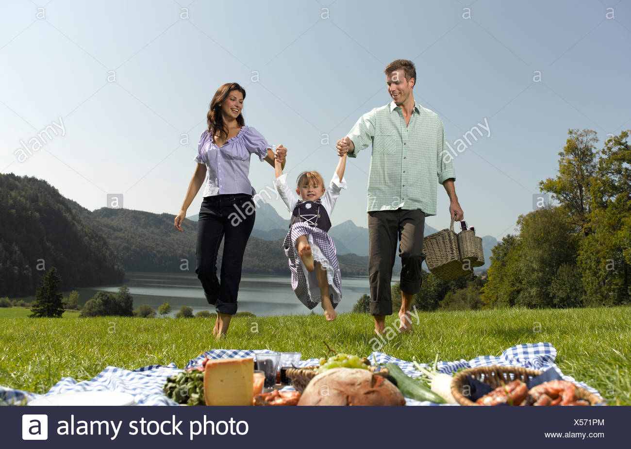 Parents walking through the grass lifting their daughter in the air - Stock Image