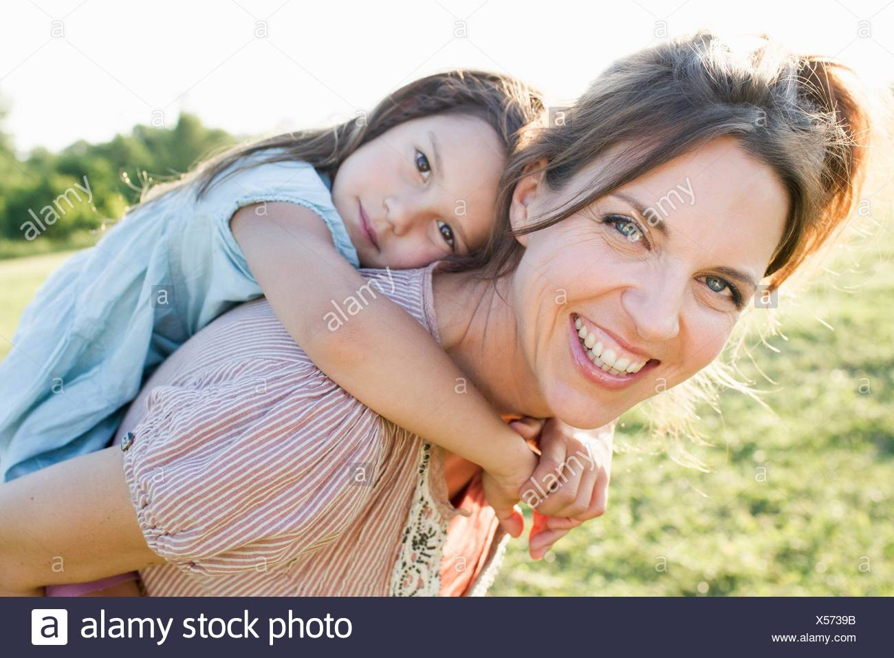 Mature woman giving daughter piggy back ride in park - Stock Image