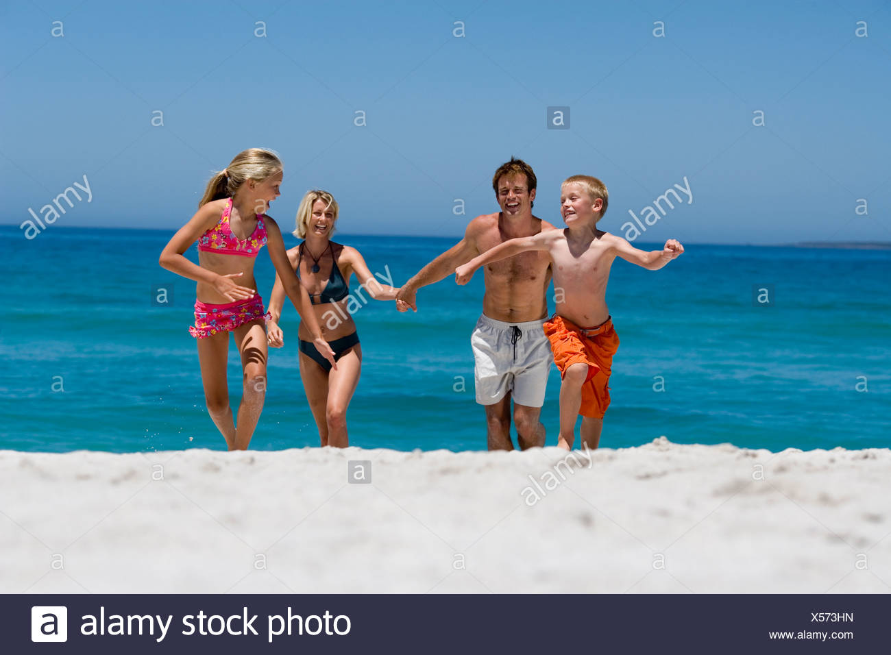 Two generation family in swimwear running from water on beach smiling front view - Stock Image