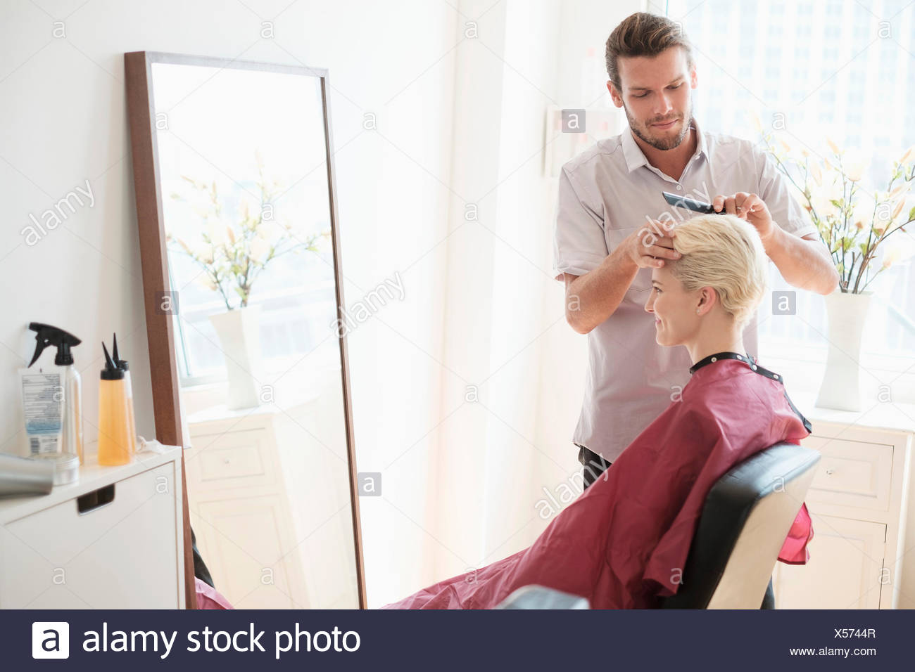 Hairdresser combing woman's hair - Stock Image
