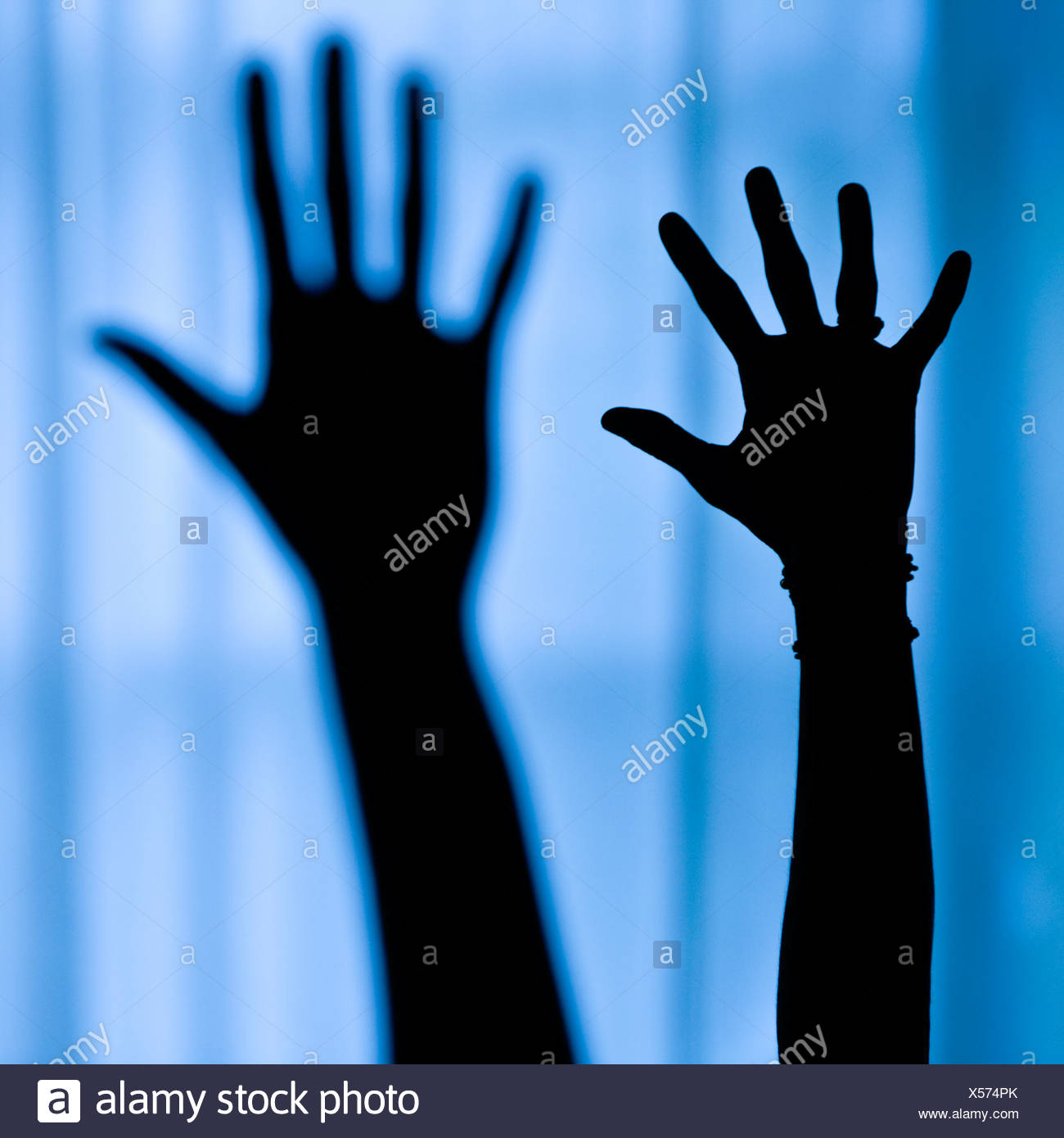 Silhouette of a person's arm raised in yoga pose - Stock Image