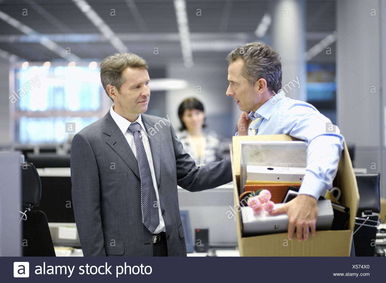 Businessman leaving office with box of personal items - Stock Image