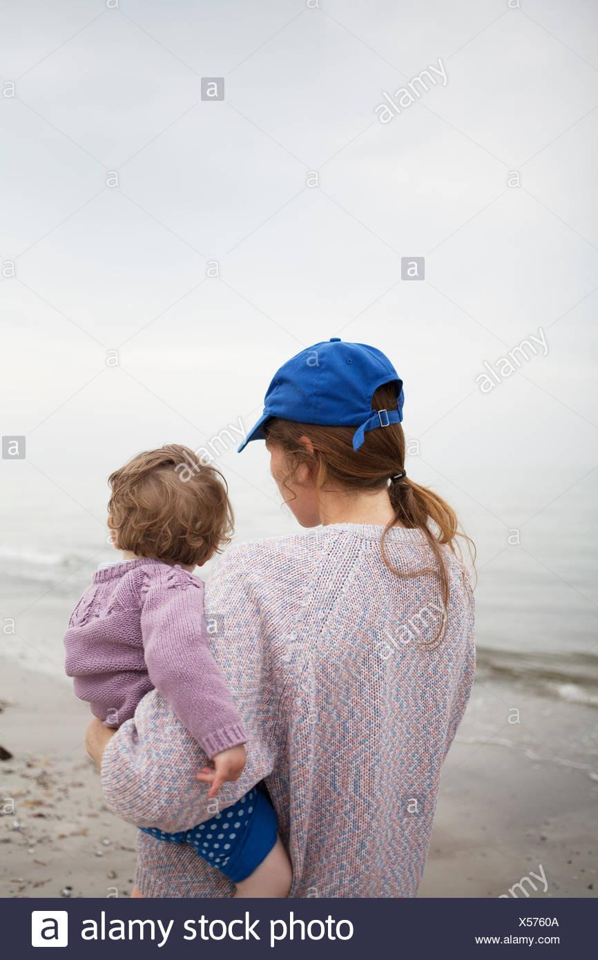 Sweden, Skane, Osterlen, Mother carrying daughter (2-3) on beach - Stock Image