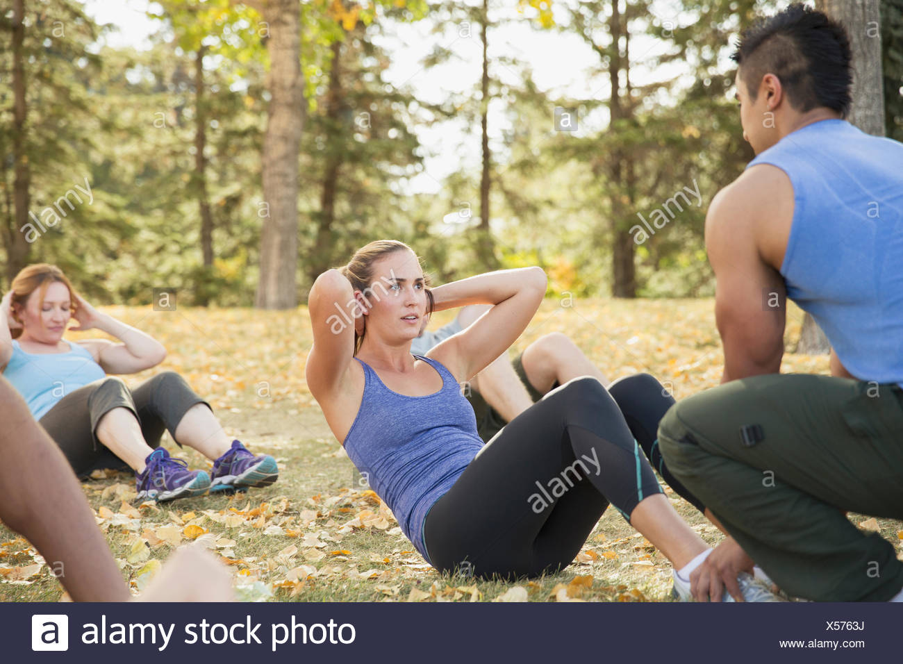 Trainer supporting woman as she does sit-ups. - Stock Image