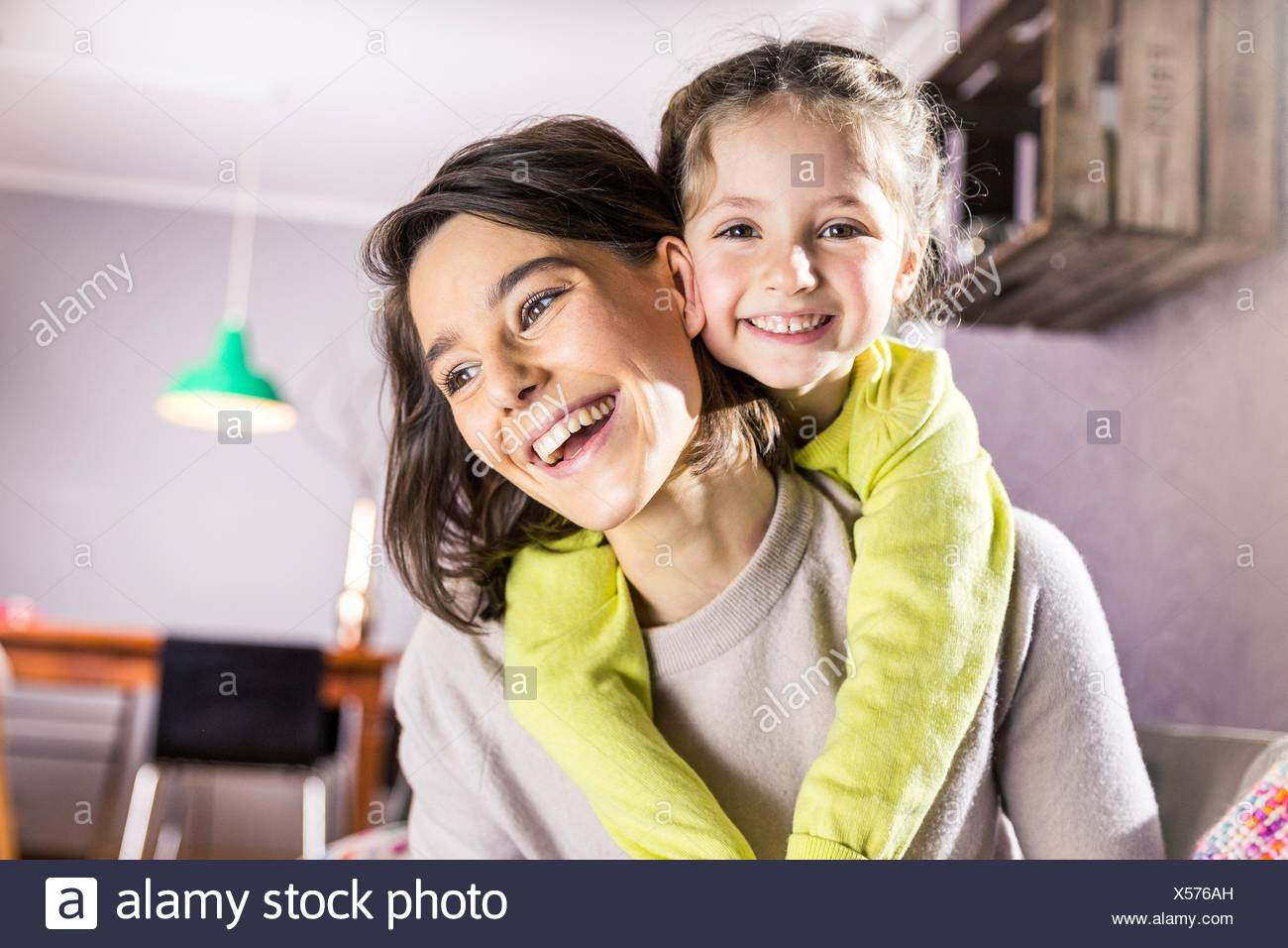 Portrait of girl getting piggyback ride from mother in living room - Stock Image