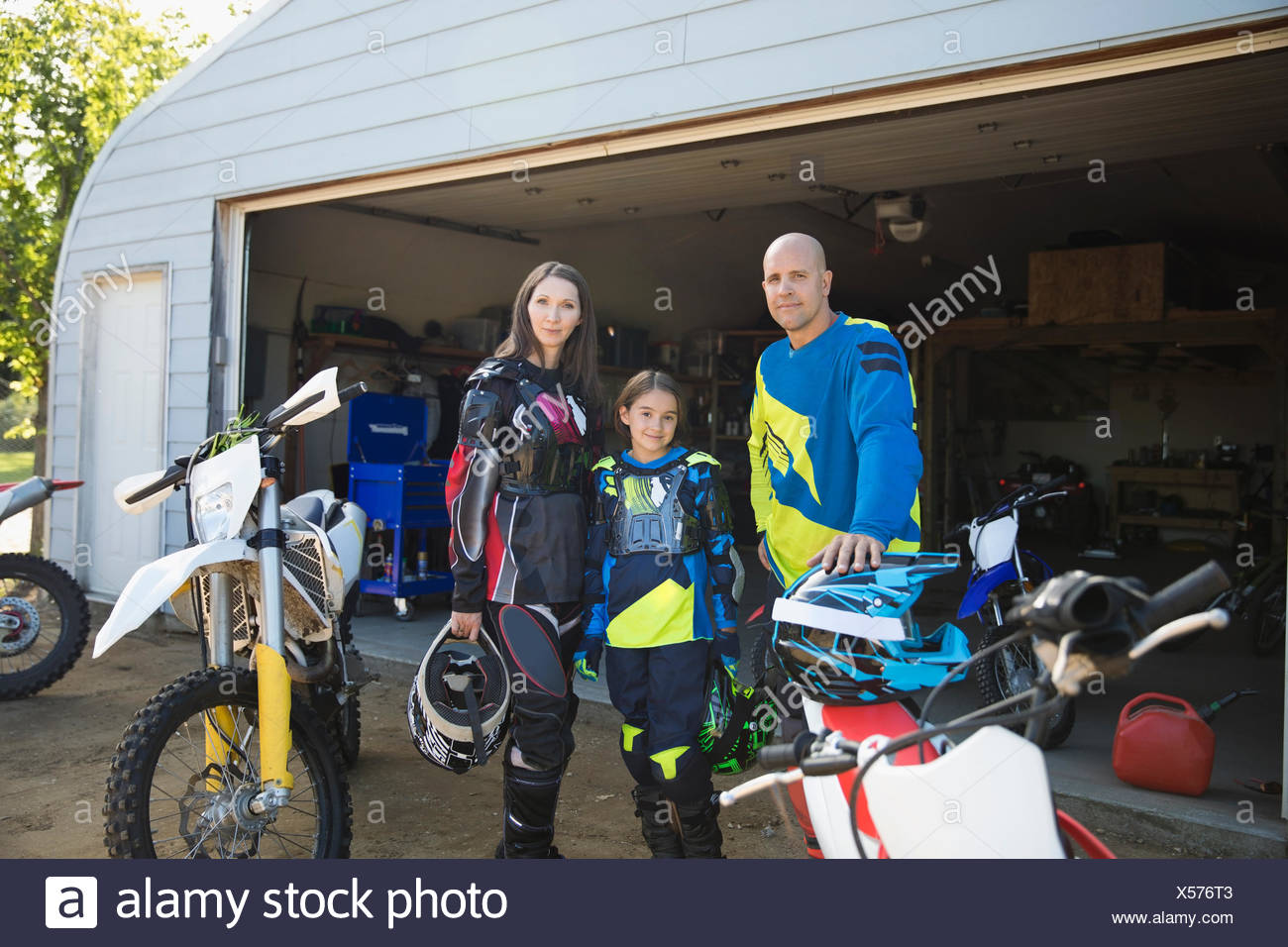 Portrait confident family near motorbikes in driveway - Stock Image