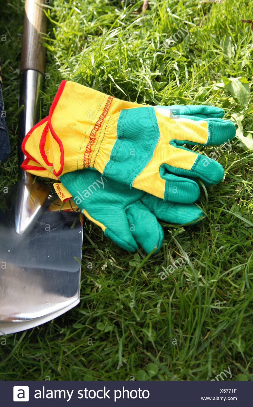 Garden gloves next to spade on a lawn - Stock Image