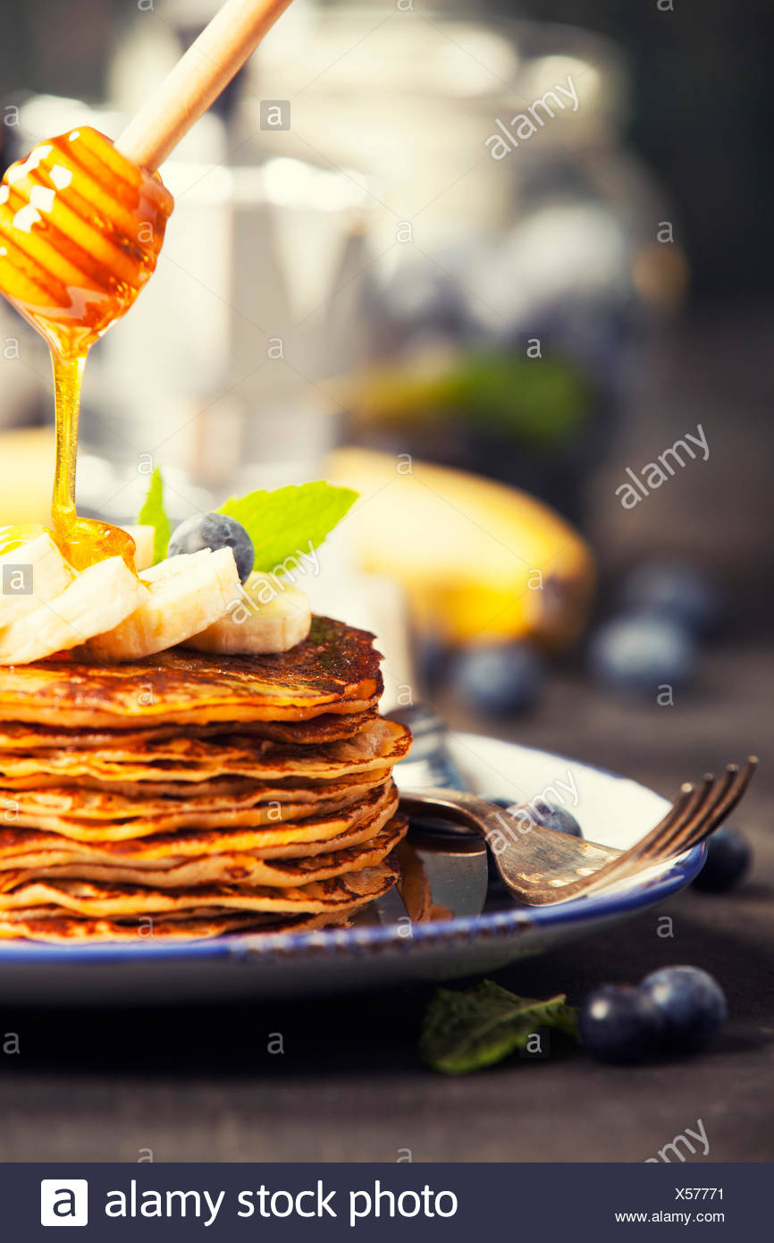 Pancake tower with fresh bananas, blueberries and honey on a rustic table Stock Photo