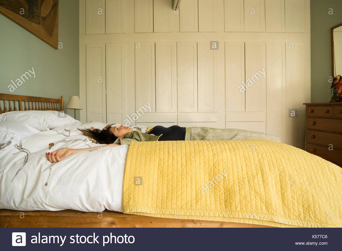 Side view of woman lying on bed with arms open - Stock Image