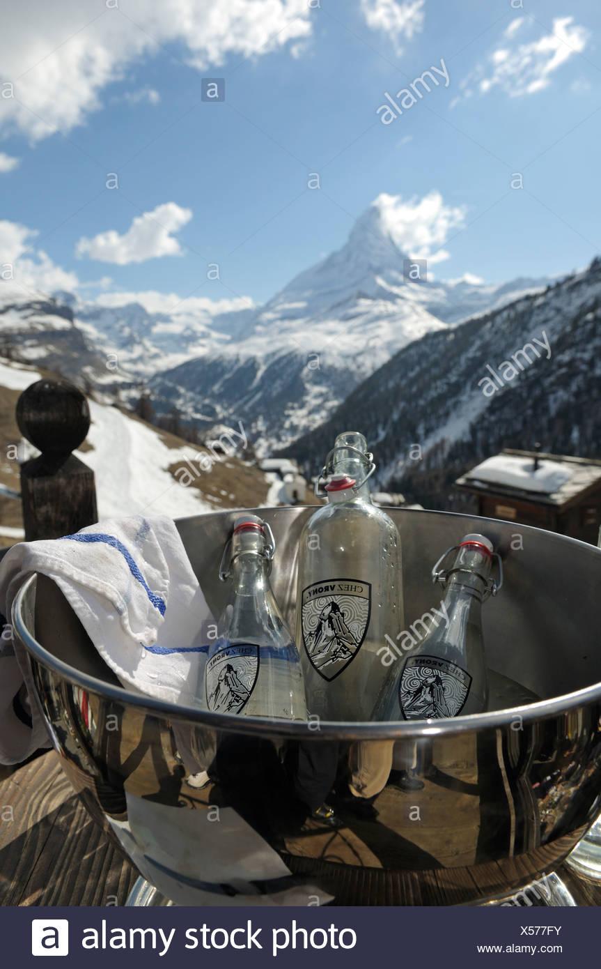 Mineral water in an ice bucket, Chalet Chez Vrony, restaurant, Mount Matterhorn at back, Zermatt, Valais, Switzerland, Europe - Stock Image
