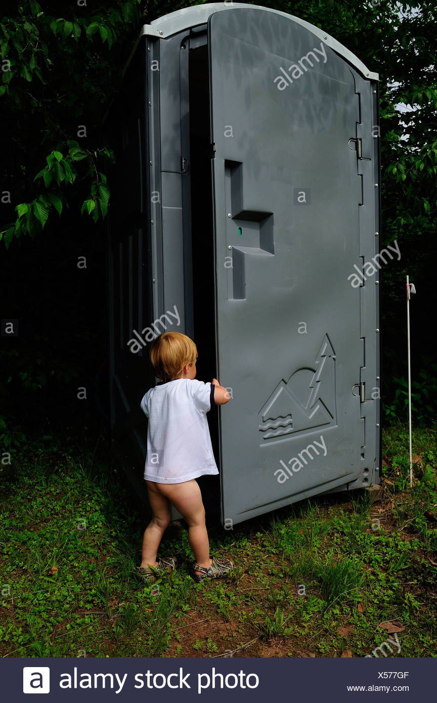 young boy opens door on portable toilet - Stock Image