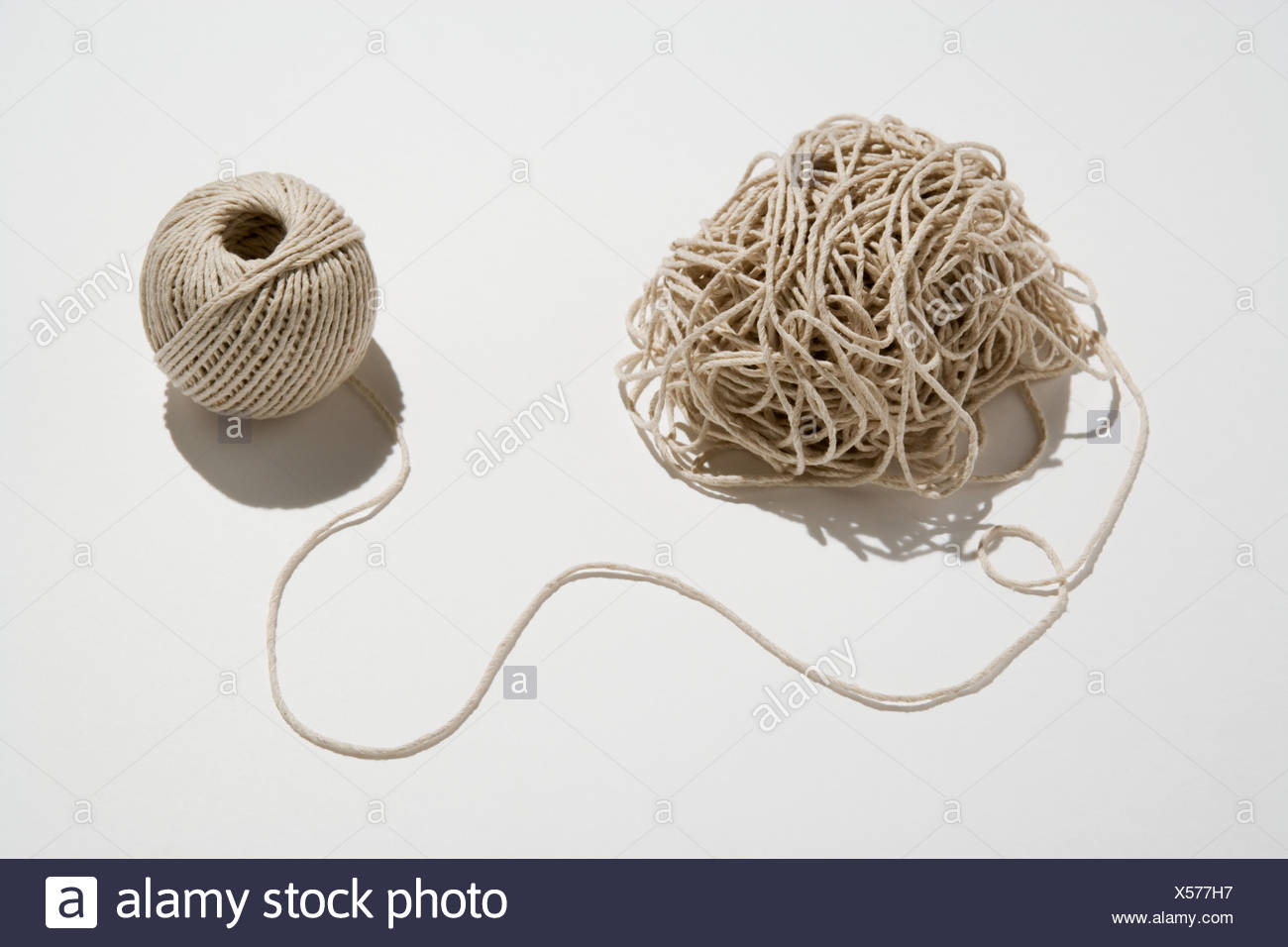 Ball of twine unraveling - Stock Image