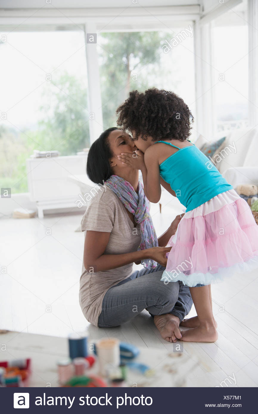 young daugher giving her mom a big kiss - Stock Image