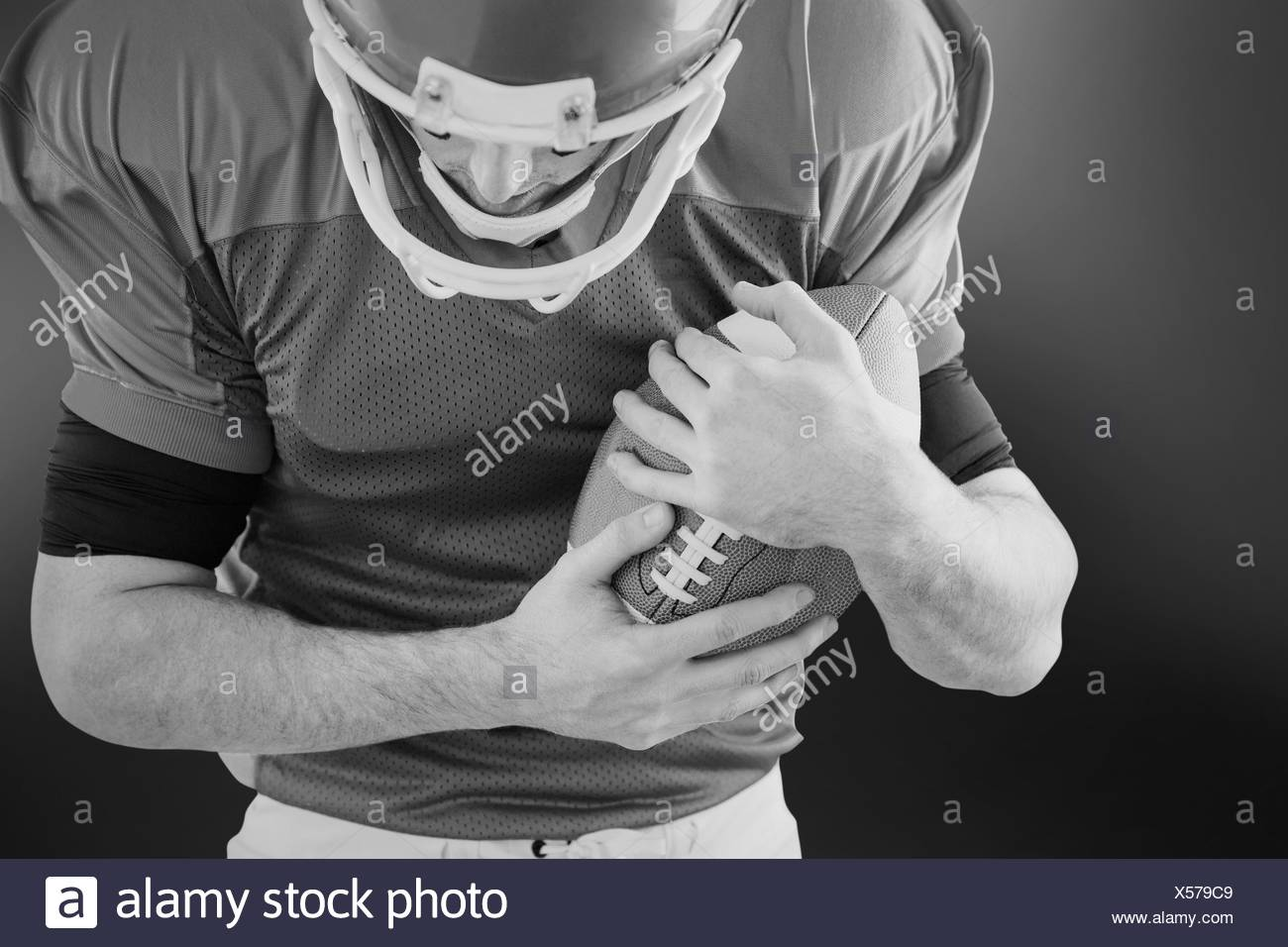 American football player protecting football - Stock Image
