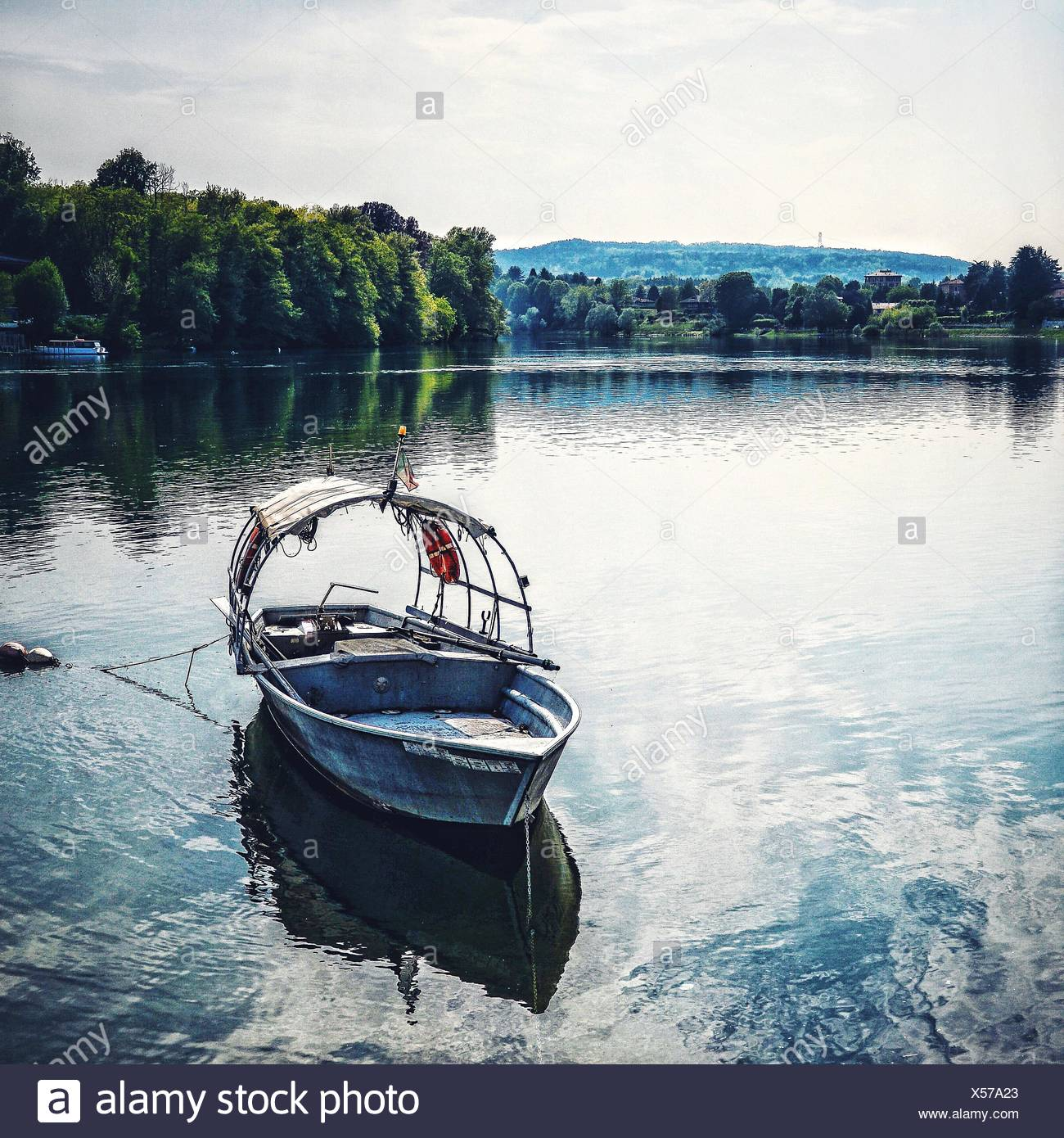 Boat Moored On Lake By Trees Against Sky - Stock Image