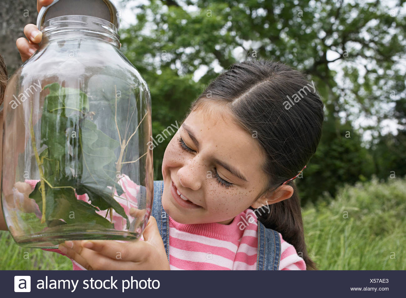 Girl (7-9) with eyes closed, holding jar of stick insects, close-up - Stock Image