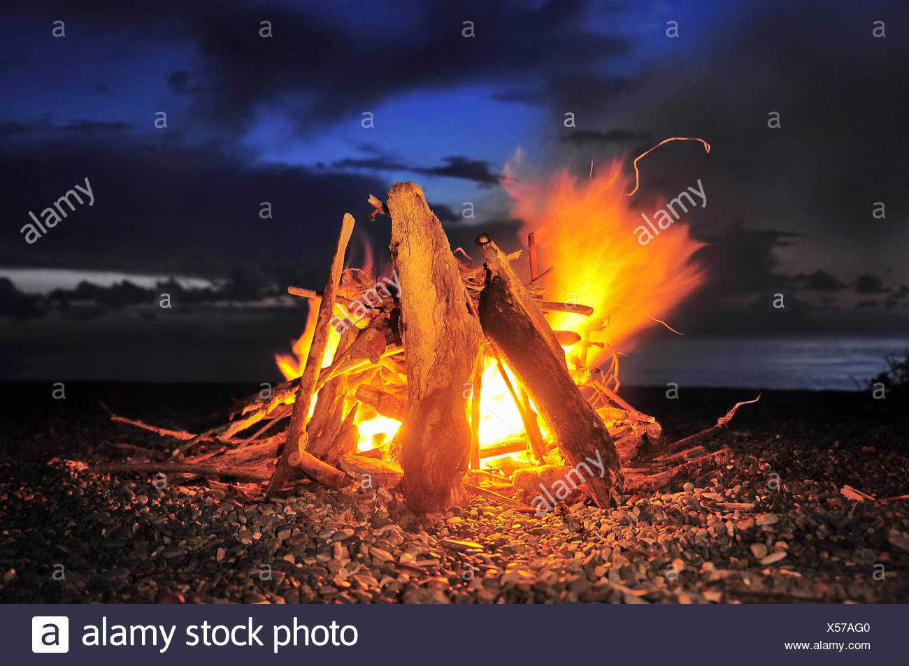 A log fire lit in an open space, with leaping flames and glowing wood and embers. - Stock Image