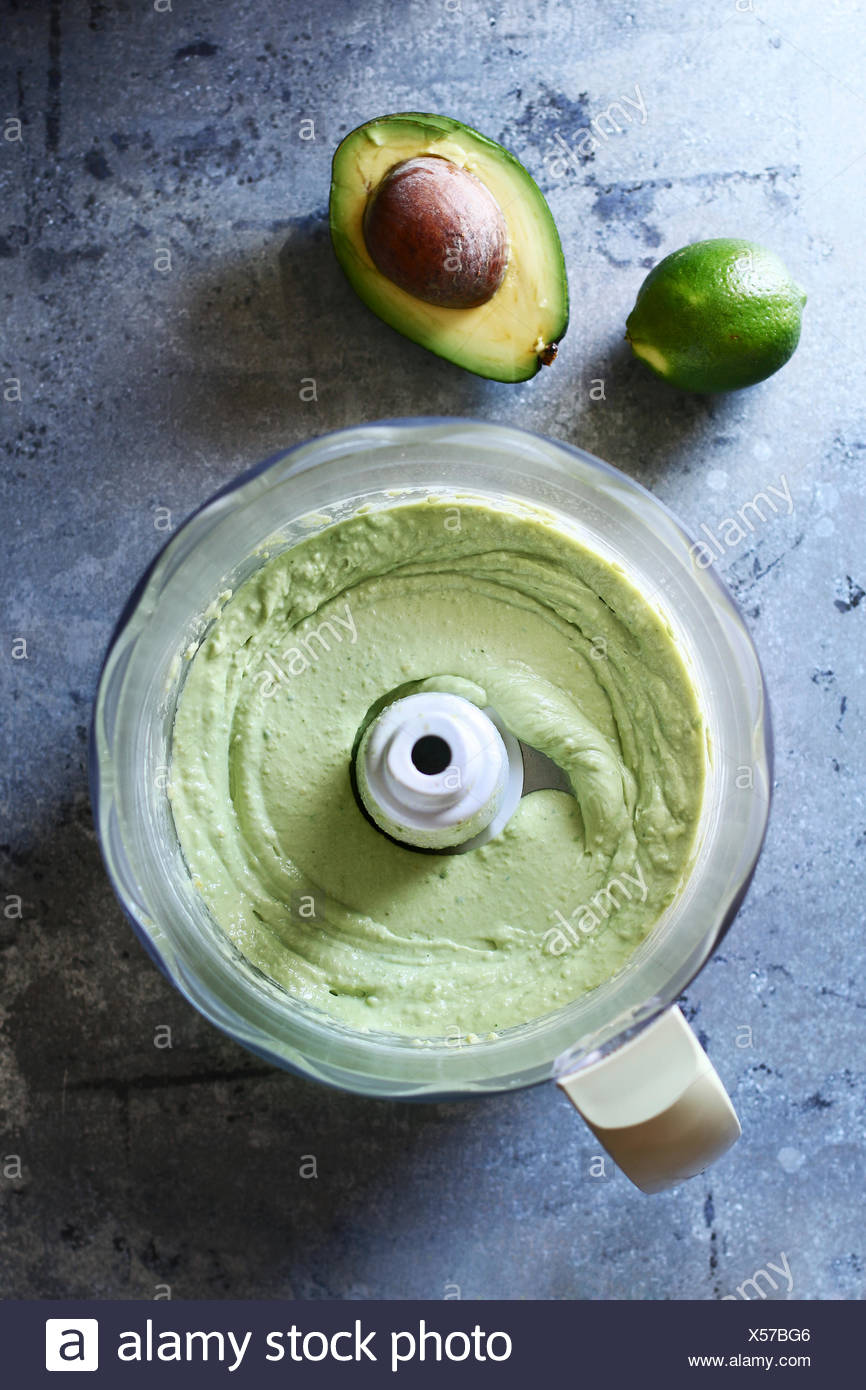Avocado lime dressing in a food processor.Top view - Stock Image