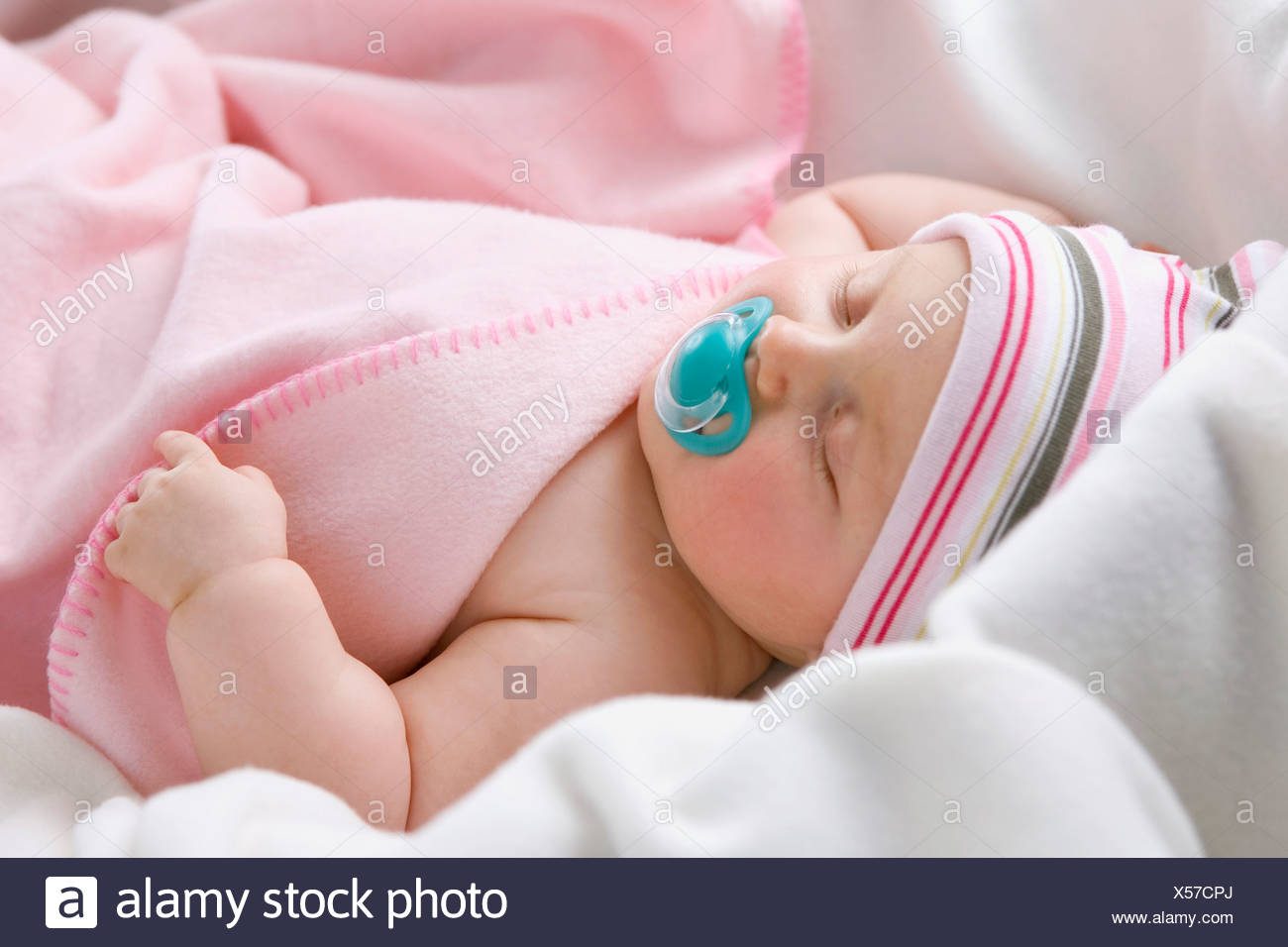 Baby boy (6-9 months) sleeping with pacifier, close-up - Stock Image
