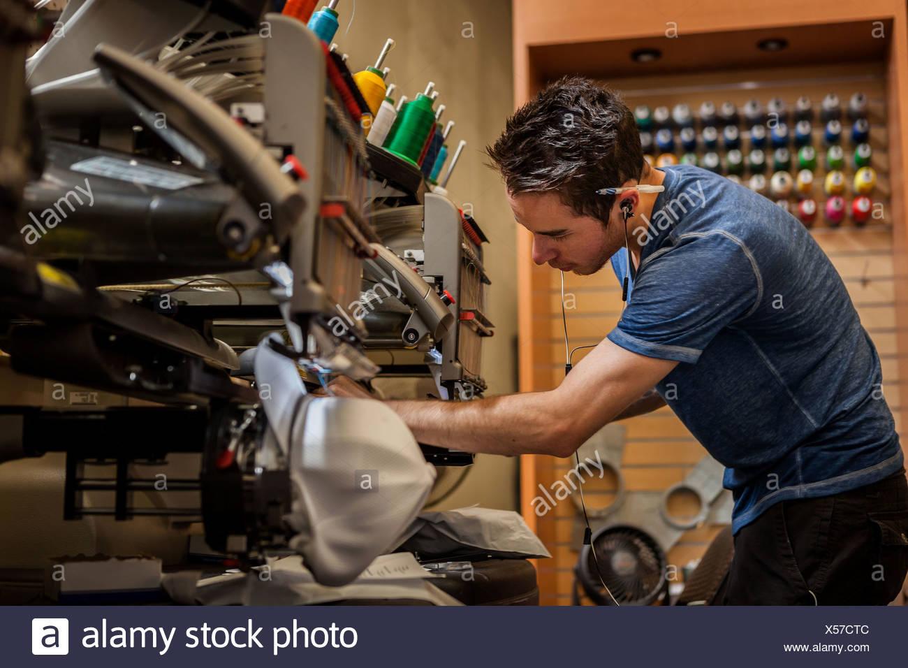 Worker preparing embroidery machine in t-shirt printing workshop - Stock Image