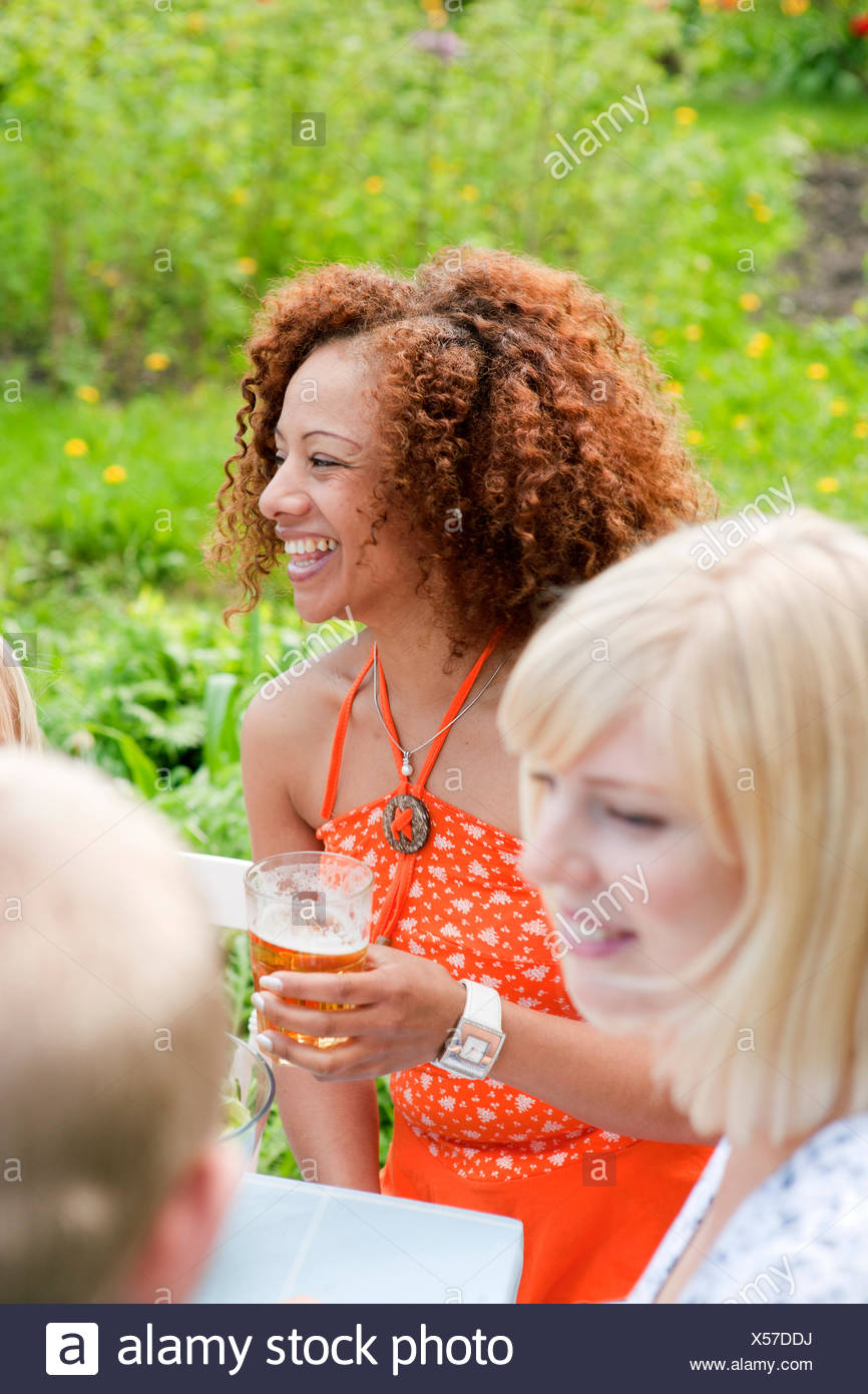 Woman with curly hair sitting at picnic table with glass of beer - Stock Image