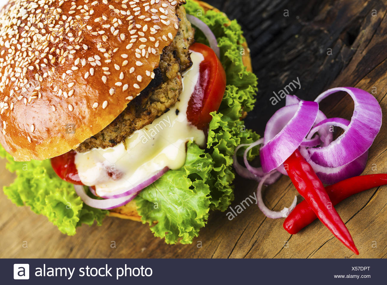Yummy Hamburger with Veggies on Wooden Table - Stock Image