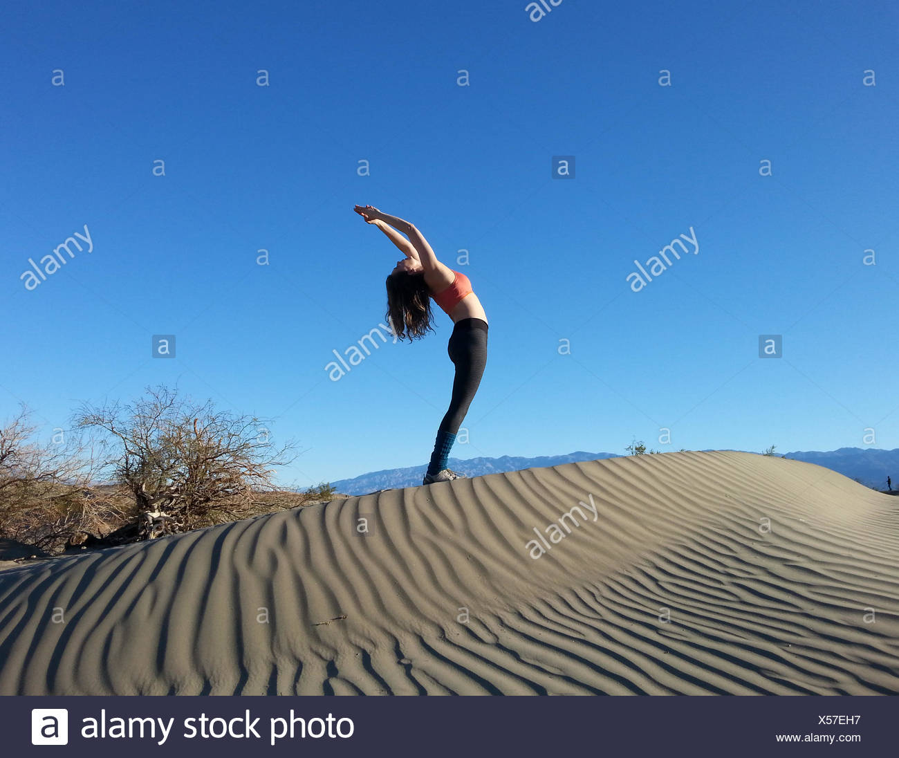 Women doing back bend on sand dune, Death Valley National Park, California, America, USA - Stock Image