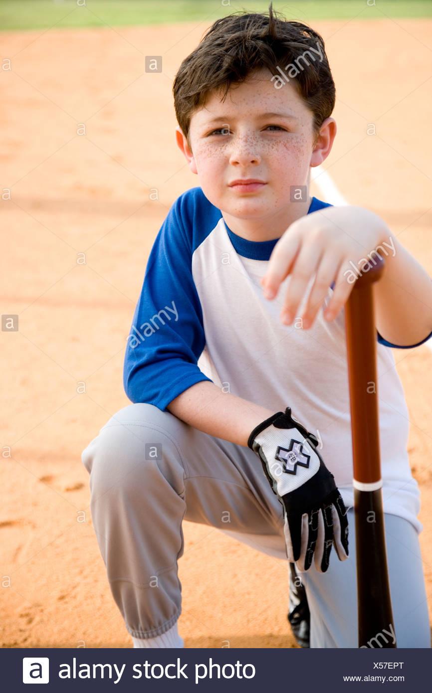 Boy with baseball bat kneeling on ground - Stock Image
