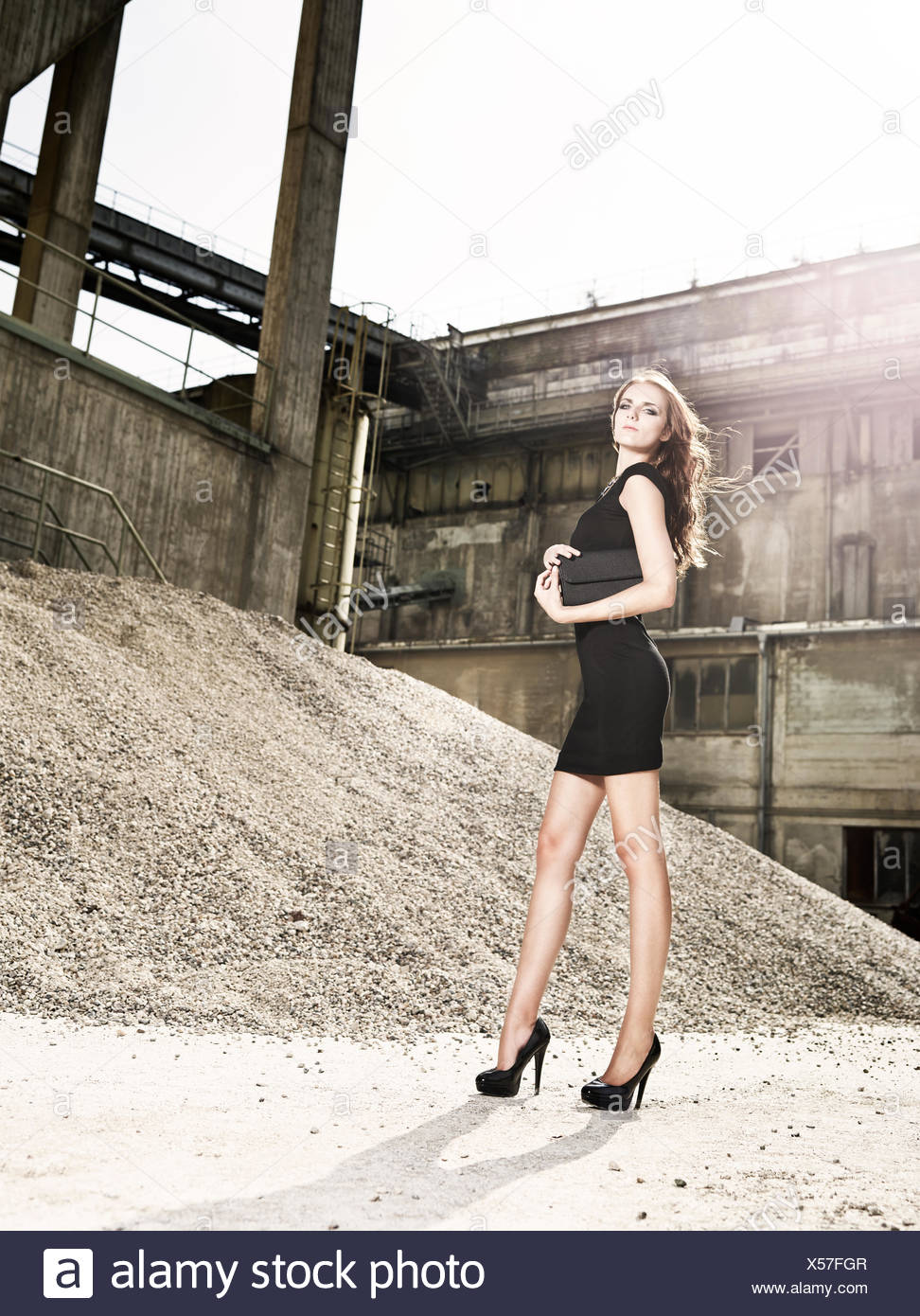 Young woman in black dress standing in front of a cement plant, jaw Felden, Bavaria, Germany - Stock Image