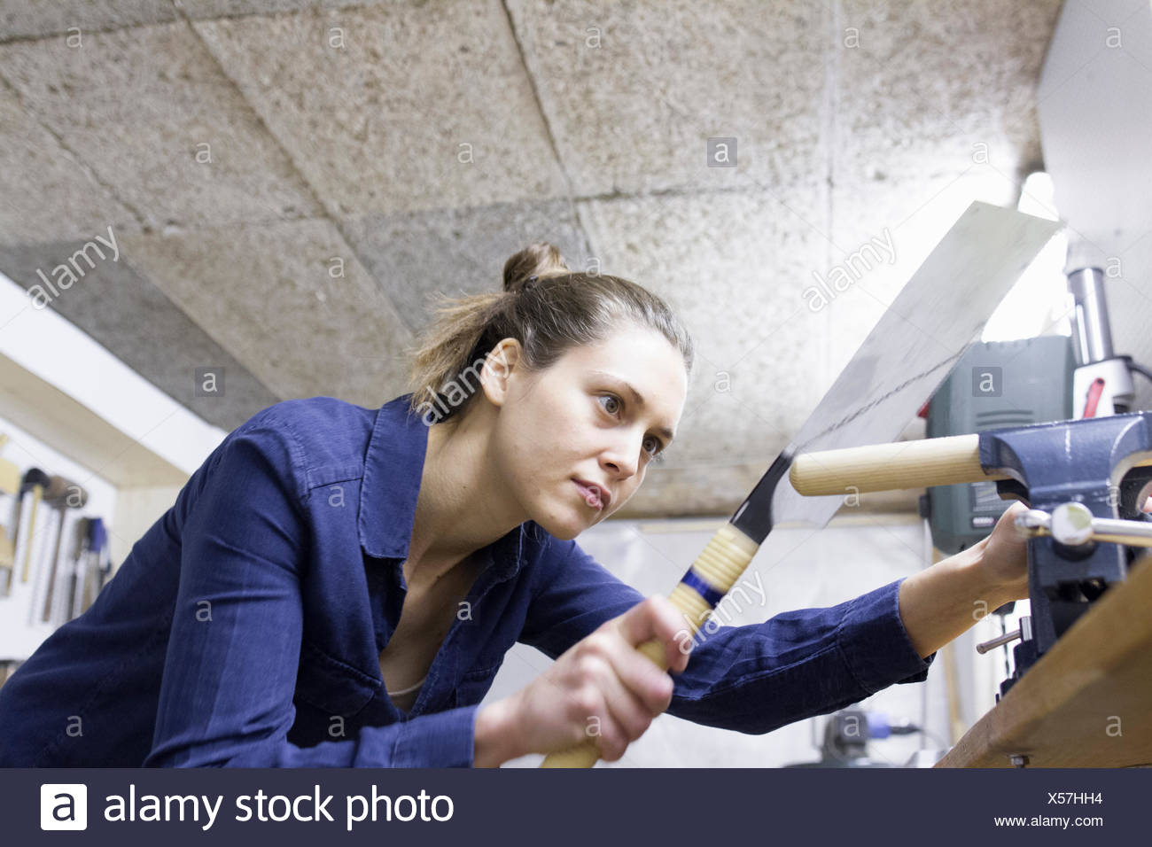 Young female carpenter shaping timber in workshop vice - Stock Image