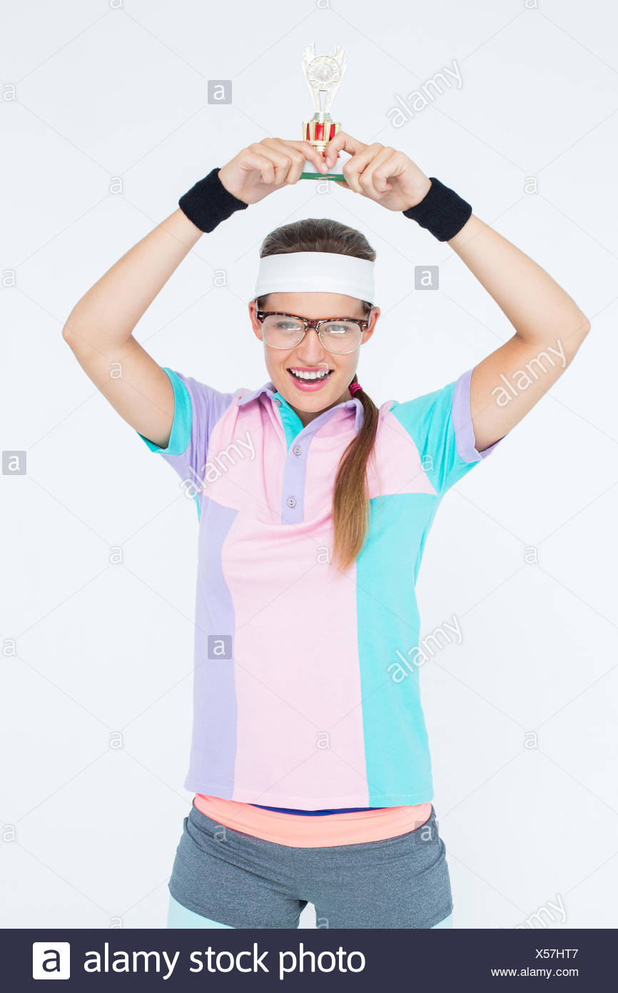 Geeky hipster holding winners trophy - Stock Image