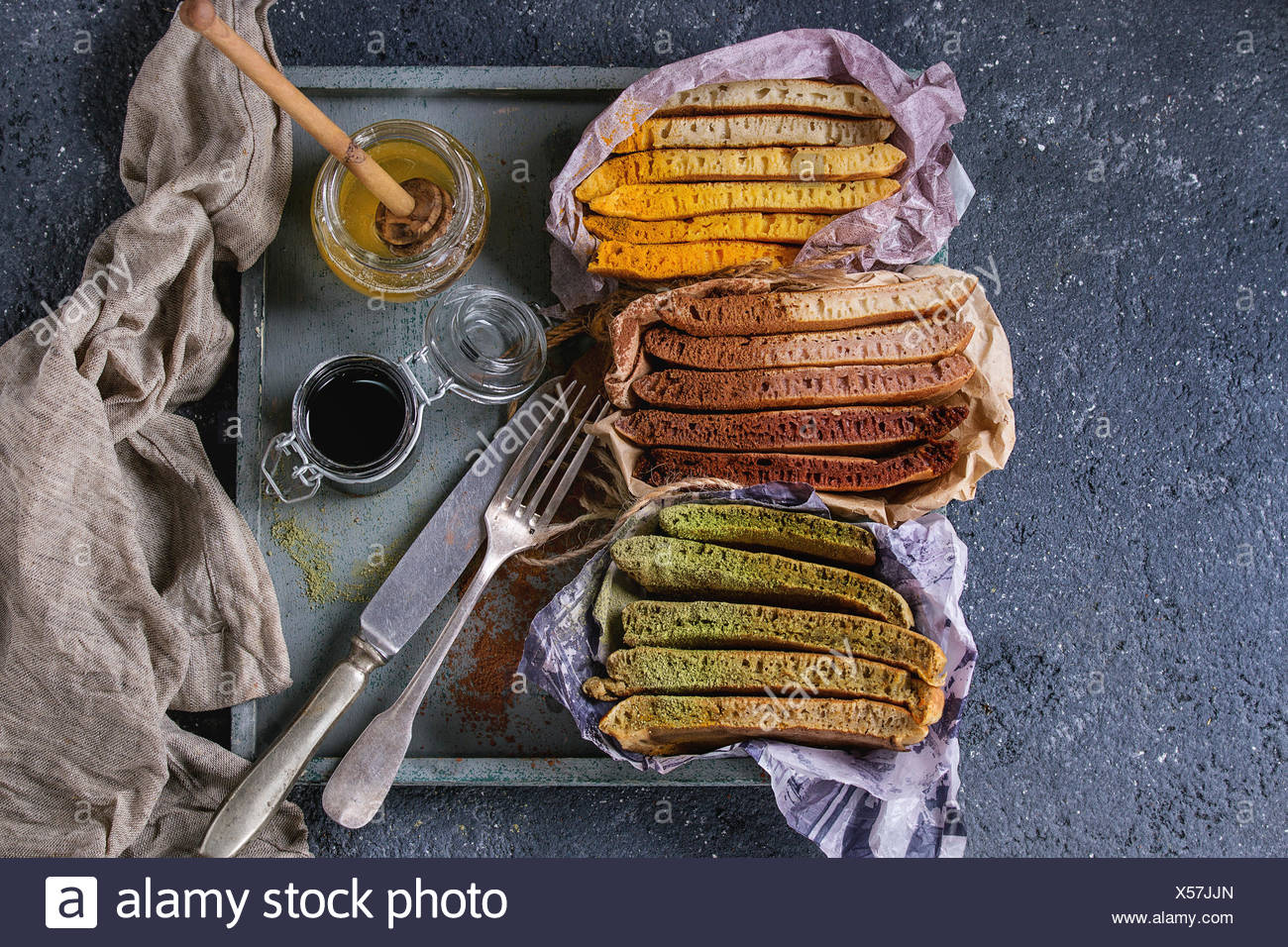 Variety of sliced american ombre chocolate, green tea matcha and turmeric pancakes served in paper paper wrapper with honey sauces on wood tray over b Stock Photo