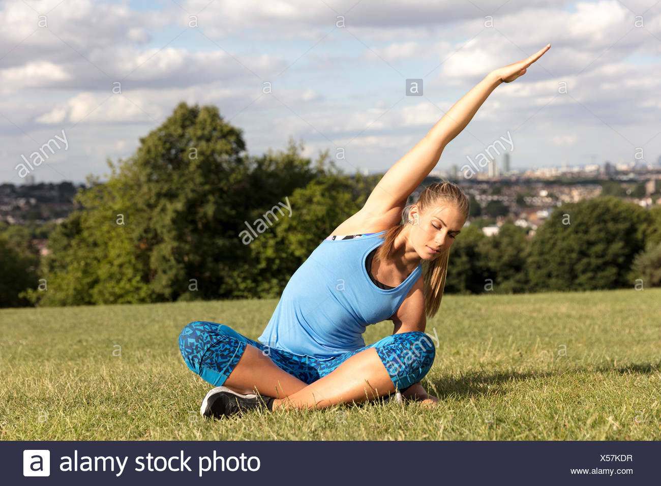 Young woman practicing yoga in park, sitting cross legged bending sideway - Stock Image