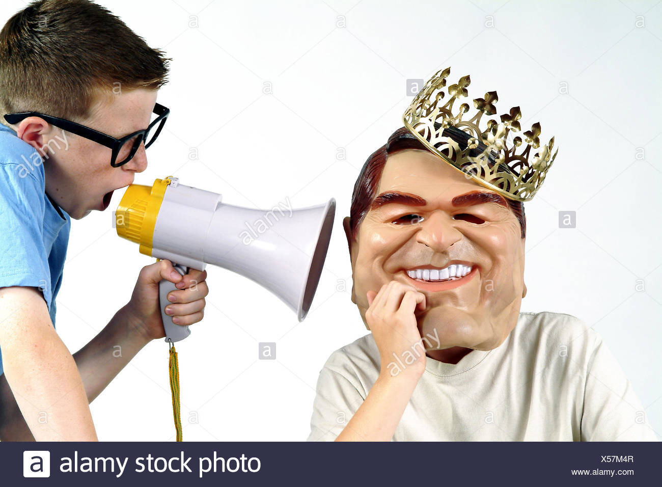 Boy, Gerhard Schröder's mask, crown, portrait, friend, glasses, megaphone, ear, shout young person, 13 years, lining, panels, mask, Gerhard Schröder, German Federal Chancellor, model, career plans, costume, costuming, joke, humor, fun, wittily, anonymity, personality, caricature, king, golden crown, signal, loudly, volume, attention, deaf, disinterest, studio - Stock Image