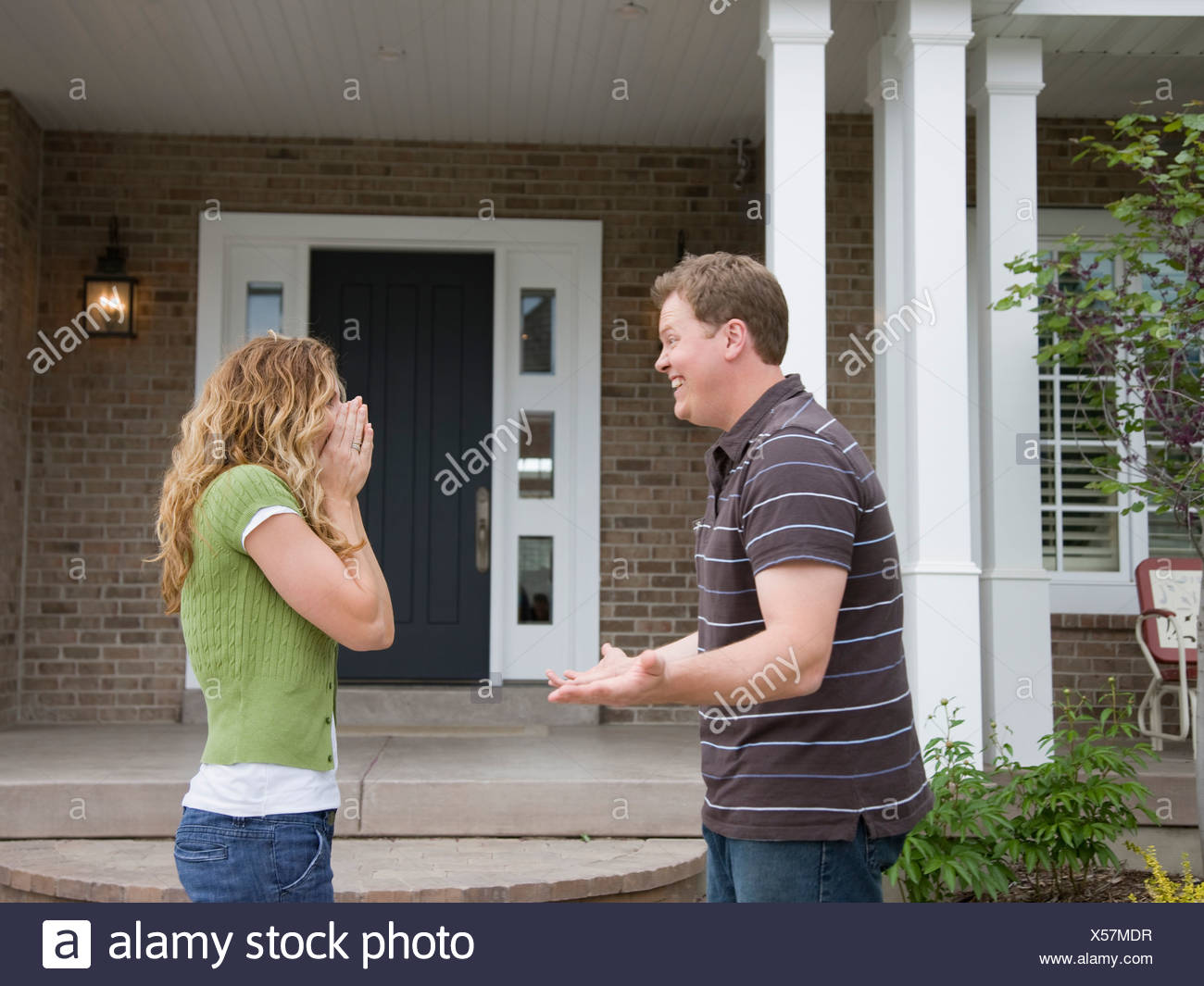man surprising wife in front of house - Stock Image
