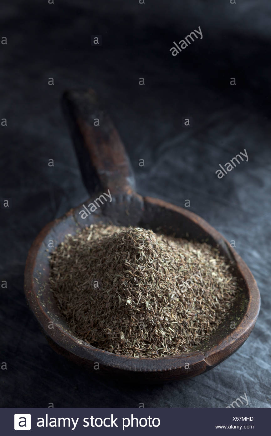 Grained thyme in wooden spoon, close up - Stock Image