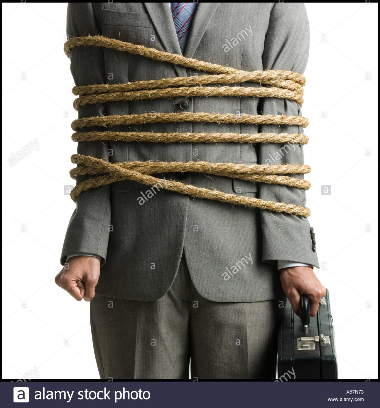 businessman in a full suit tied up with a rope around his mid section Stock Photo