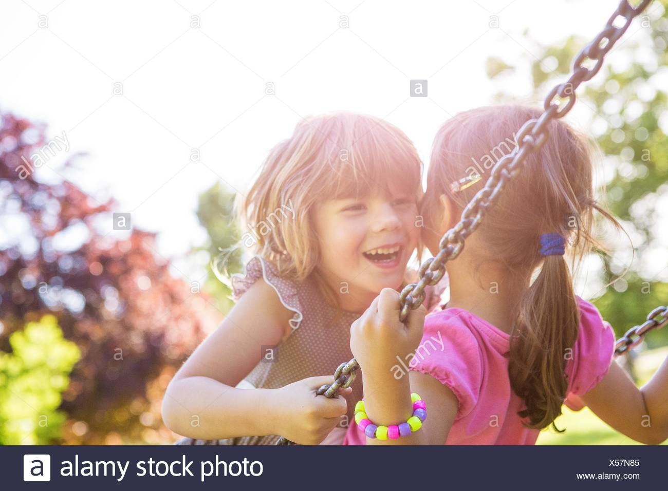 Two young girls swinging face to face on park swing - Stock Image