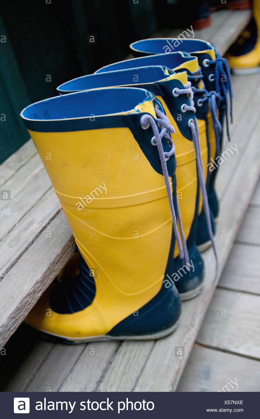 two pairs of yellow rain boots with blue trim; tofino, british columbia, canada - Stock Image