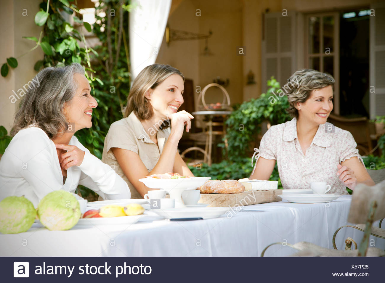 Spain, Mallorca, three female friends sitting at laid table in the garden - Stock Image