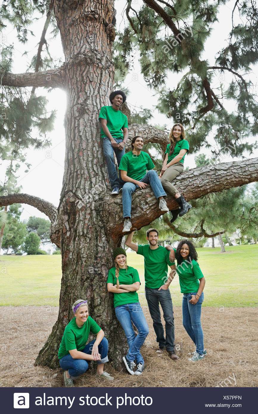 Group of happy environmentalists by tree in park - Stock Image