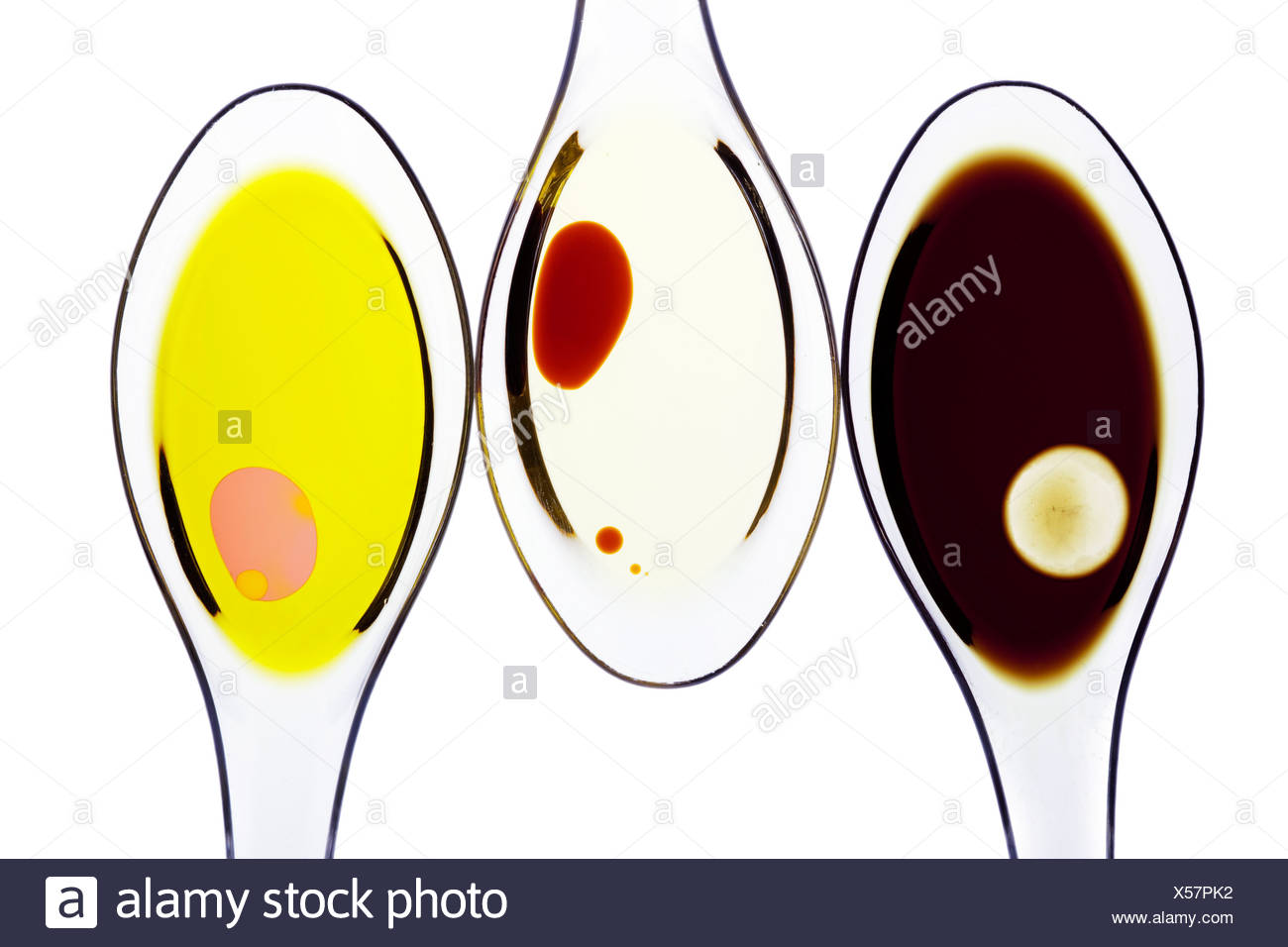 Different kinds of oil, core oil, pistachio oil, olive oil and vinegar on clear spoons - Stock Image