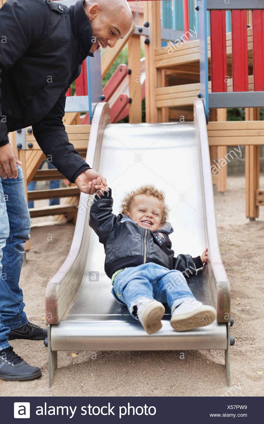 Dad plays with son (2-3) in playground - Stock Image