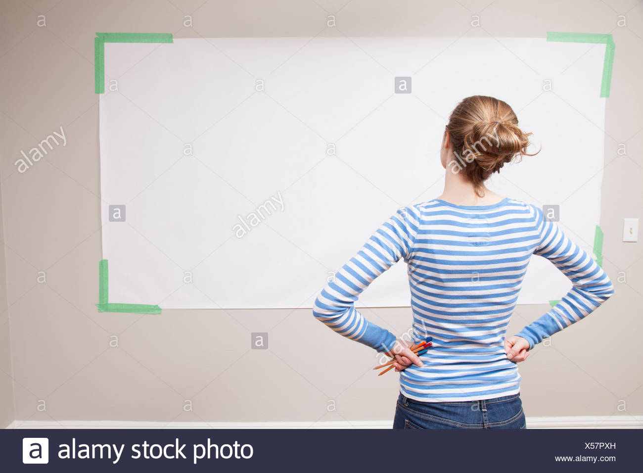 Girl looking at blank space on wall - Stock Image