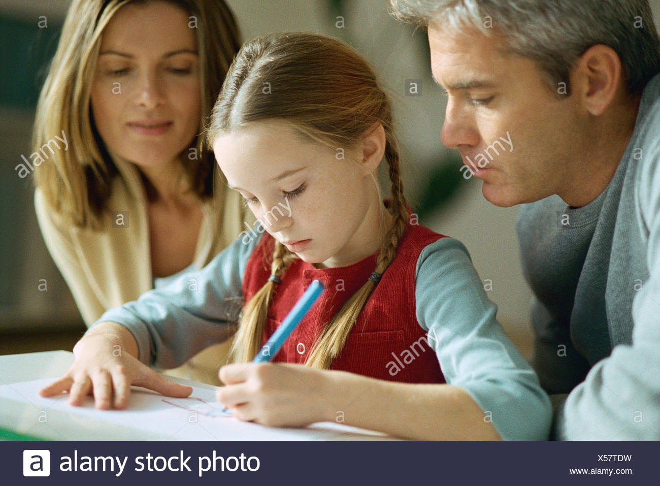Little girl drawing, parents sitting on either side, watching over her shoulder Stock Photo